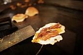 Spiegelei mit Bacon auf Kochplatte im Restaurant