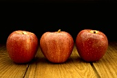 Three Red Apples on a Wood Table