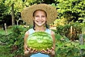 Young Girl Holding a Freshly Picked Watermelon; In Garden