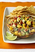 Bowl of Fresh Mango Salsa on a Platter with Tortilla Chips