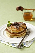 Small Stack of Pancakes Topped with Chocolate Shavings; Syrup with Honey Dipper
