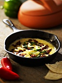Queso Fundido (Mexican Cheese Dish) with a Onions in a Cast Iron Skillet
