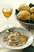 Single Serving of Chicken ala King; Basket of Biscuits; Glass of White Wine