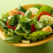 Simple Salad with Romain Lettuce, Cucumber, Red Pepper and Croutons; In a Yellow Bowl