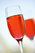 Two Pomegranate Bellinis in Champagne Flutes