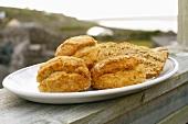 Scones und Brot auf Holzzaun am Meer (Aran Island, Irland)