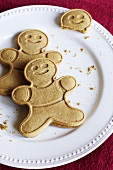 Two Whole Gingerbread Men and One Gingerbread Man Head; On a White Plate
