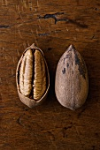 Cracked Pecan and Whole Pecan in Shell on Wooden Table