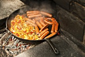 Hot Dogs, Onions and Peppers Cooking in a Cast Iron Skillet Over an Outdoor Fire
