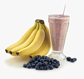 Acai Shake in a Glass with Straw; Bananas and Blueberries; White Background