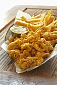 Fried Clams with French Fries and Tarter Sauce in Rustic Table