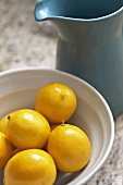 White Bowl Filled with Lemons; Blue Pitcher