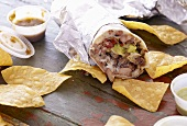 Large Burrito Wrapped in Foil with Tortilla Chips and Salsas