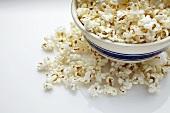 Bowl of Popcorn; Popcorn Spilled Around Bowl; White Background