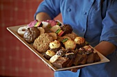 Chef Carrying a Large Platter of Assorted Custom Made Cookies and Pastries