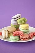 Macarons in verschiedenen Pastellfarben, einige angebissen