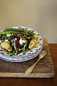 A mixed leaf salad with fried artichokes, asparagus, goat's cheese and pistachios