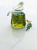 Mit Kräutern und Knoblauch aromatisiertes Öl im Glas