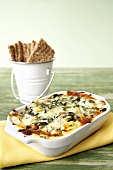 Warm Spinach Dip in Baking Dish with Crackers in a Pail