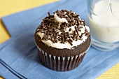 Chocolate Cupcake with Vanilla Frosting and Chocolate Sprinkles; Glass of Milk
