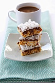Three Almond Chocolate Coconut Bars; Stacked; Cup of Coffee