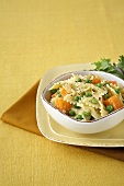 Farfalle Pasta with Peas and Squash in a Bowl; Side Salad
