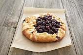 Rustic Cherry Pie on Paper on a Wooden Table