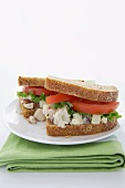 Chicken Salad Sandwich with Lettuce and Tomato on Wheat Bread; Halved on a Plate