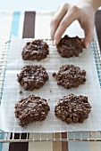 Hand Grabbing a Chocolate Oatmeal Cookie from Cooling Rack
