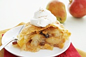 Slice of Apple and Raisin Pie with Whipped Cream on a Plate with Fork