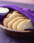 Sliced white bread in a wooden bowl covered with a cloth