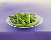Fresh Pea Pods on a Plate; One Split Open to Show Peas