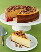 Slice of Pumpkin Cheesecake with Nut Topping; Whole Cheesecake with Slice Removed in Background