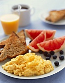 Breakfast Plate with Scrambled Eggs, Whole Wheat Toast, Fresh Fruit and a Glass of Orange Juice