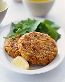 Two Corn and Chickpea Patties on a Plate with Lemon and Greens