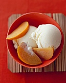 Sliced Persimmon Over Vanilla Ice Cream; In a Bowl; From Above