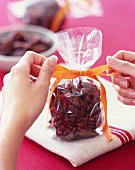 Hands Tying a Ribbon onto a Gift Bag of Candied Pecans