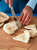 Person Slicing Pita Bread into Triangles