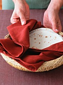 Hands Holding a Basket of Warmed Tortillas Wrapped in a Towel