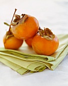 Persimmons on Folded Green Linen