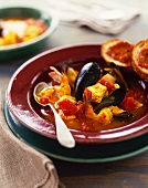 Bowl of Seafood Bouillabaisse with a Spoon and Bread