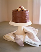 Frosted Chocolate Cake Topped with White and Milk Chocolate Curls; On a Pedestal Dish