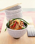 Asian Noodles with Chicken and Vegetables in a Bowl; Stacked Bowls and Chopsticks in the Background