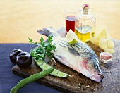 Assorted Fresh Ingredients on a Cutting Board; Whole Fish, Plums, Beans, Garlic, Olive Oil and Vinegar