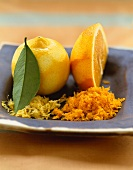 A Lemon and Orange with Grated Lemon and Orange Rinds on a Dish