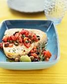 Swordfish Fillet Topped with Tomato and Caper Sauce; In a Blue Bowl