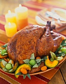 Whole Roast Turkey on a Platter with Squash and Kumquats; On a Table with Candles