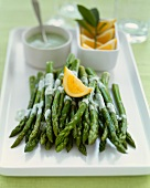 Asparagus Spears with Herb Sauce and an Orange Wedge