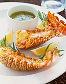 Two Lobster Tails on a White Plate with Lemon Wedges and Dipping Sauce