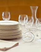 Stacked White Plates and Empty Stem Glasses